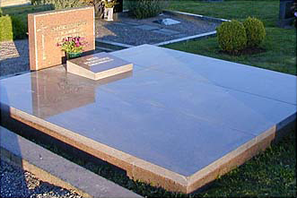 Polerad liggare i svensk granit pulpetform placerad med gravlock.